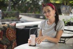 Stående av den härliga unga brunettmodellen i kafé nära vägen som sitter på tabellen royaltyfria foton