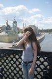 Stående av den härliga unga flickan på bakgrunden för blå himmel för bro med att blåsa hår i vind Arkivbilder