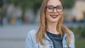 Stående av den härliga unga hipsterkvinnan i exponeringsglas genom att använda hennes mobiltelefon i gatan Steadicam ultrarapidsk arkivfilmer