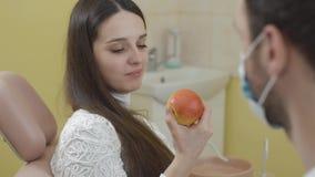 Stående av den härliga unga kvinnan i den tand- stolen Flicka som äter en Apple och ser kameran Begreppet av stock video