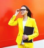 Stående av den härliga unga kvinnan i exponeringsglas, gul dräkt Arkivfoto