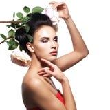 Stående av den härliga unga kvinnan med blommor i hår Arkivfoton
