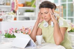 Stående av den härliga unga kvinnan med huvudvärk genom att använda den digitala minnestavlan arkivfoton