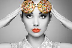 Stående av den härliga unga kvinnan med kulöra exponeringsglas royaltyfri foto