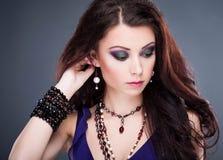 Stående av den härliga unga kvinnan med länge färgat brunt hår a Arkivfoto