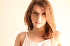 Stående av den härliga unga kvinnan med långt brunt hår som poserar på vit bakgrund Arkivbild
