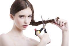 Stående av den härliga unga kvinnan med sax som klipper hennes hår över vit bakgrund royaltyfri fotografi