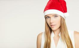 Stående av den härliga unga kvinnan som bär den Santa Claus hatten Arkivfoton