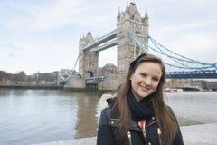 Stående av den härliga unga kvinnan som framme står av tornbron, London, UK Arkivfoto