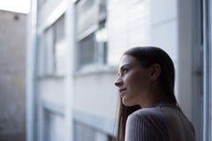 Stående av den härliga unga kvinnan som håller ögonen på till och med fönstret Arkivfoton