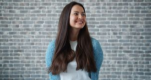 Stående av den härliga unga kvinnan som ler på bakgrund för tegelstenvägg arkivfilmer