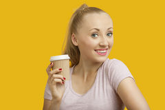 Stående av den härliga unga kvinnan som rymmer den disponibla koppen över gul bakgrund Royaltyfri Fotografi