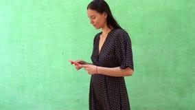 Stående av den härliga unga kvinnan som rymmer den smarta telefonen på grön bakgrund med kopieringsutrymme stock video
