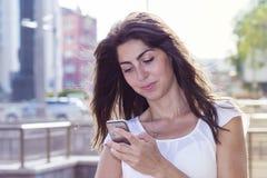 Stående av den härliga unga kvinnan som ser hennes telefon Arkivfoto