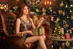 Stående av den härliga unga kvinnan som sitter i rum som dekoreras till jul royaltyfri fotografi
