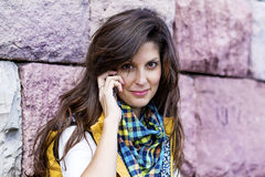 Stående av den härliga unga kvinnan som talar på den utomhus- telefonen Royaltyfria Bilder
