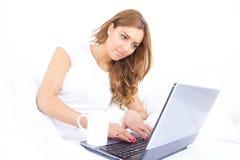 Stående av den härliga unga kvinnlign som hemma använder en bärbar dator Arkivbilder