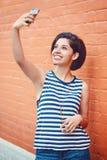 Stående av den härliga unga latinska latinamerikanska flickakvinnan utanför danandeselfiefotoet med mobiltelefonen Arkivfoton