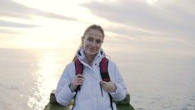 Stående av den härliga unga le kvinnan i omslag med ryggsäcken på pir med havet på en bakgrund arkivfilmer