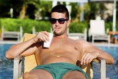 Stående av den härliga unga mannen som dricker fruktsaft på pölen Arkivfoton