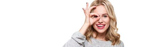 Stående av den härliga upphetsade kvinnan i tillfälliga kläder som ler och visar det ok tecknet på kameran som isoleras över vit  royaltyfri bild