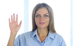 Stående av den härliga vinkande handen för ung kvinna till välkomnandet lager videofilmer