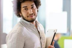 Stående av den hållande bärbara datorn för säker ung affärsman på kontoret Arkivbild