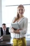 Stående av den hållande minnestavlaPC:N för säker ung affärskvinna med affärsmannen i bakgrund på kontoret Arkivfoton
