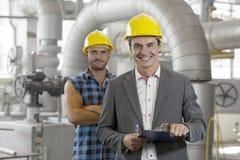 Stående av den hållande skrivplattan för ung manlig arbetsledare med den manuella arbetaren i bakgrund på bransch Arkivfoton