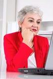Stående av den höga affärskvinnan med bärbara datorn på arbetsplats Arkivbild