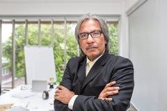Stående av den höga affärsmannen i kontoret Hög asiatisk affärsman på en mötesrum arkivfoton