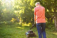 Stående av den höga gamala mannen som använder gräsklipparen i trädgården på sommardag royaltyfria foton