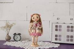 Stående av den handgjorda tappningdockan för textil med gröna ögon, långt brunt hår i ljus - rosa textilklänning med det försikti Arkivbilder