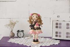 Stående av den handgjorda tappningdockan för textil med gröna ögon, långt brunt lockigt hår i ljus - rosa färger och blåtttextile Royaltyfria Bilder