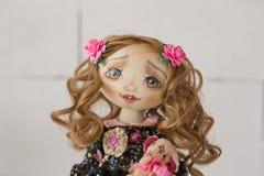 Stående av den handgjorda tappningdockan för textil med gröna ögon, långt brunt lockigt hår i ljus - rosa färger och blåtttextile Royaltyfri Foto