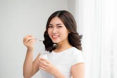 Stående av den hemmastadda ätayoghurten för ung asiatisk kvinna royaltyfri bild