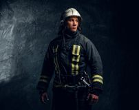 Stående av den iklädda likformign för brandman och säkerhetshjälmen som från sidan ser med en säker blick arkivbild