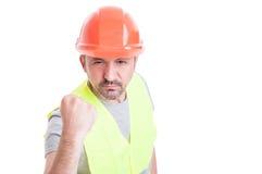 Stående av den ilskna arbetaren som visar hans näve arkivfoton