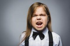 Stående av den ilskna flickan som isoleras på grå bakgrund Negativ mänsklig sinnesrörelse, ansiktsuttryck closeup royaltyfri fotografi
