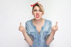 Stående av den ilskna härliga unga kvinnan i blå grov bomullstvillskjorta och rött huvudbindelanseende med dåligt lynne och se ka royaltyfri bild