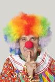 Stående av den ilskna höga manliga clownen med fingret på hakan över ljus - grå bakgrund Royaltyfri Fotografi