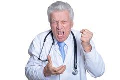 St?ende av den ilskna h?ga manliga doktorn med den isolerade stetoskopet arkivbild