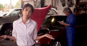 Stående av den ilskna kunden, medan en mekaniker arbetar på en bil i bakgrunden lager videofilmer