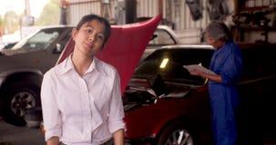 Stående av den ilskna kunden, medan en mekaniker arbetar på en bil i bakgrunden arkivfilmer