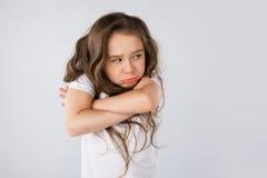 Stående av den ilskna och ledsna lilla flickan som isoleras på vit bakgrund royaltyfri bild