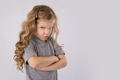 Stående av den ilskna och ledsna lilla flickan som isoleras på vit bakgrund arkivfoto