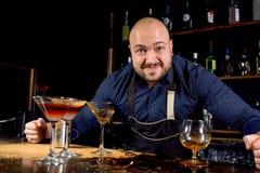 Stående av den ilskna och stressade bartendern med bowtie bak stången med alkoholdrycker omkring Stressig livsstil av arkivbilder
