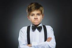 Stående av den ilskna pojken på grå bakgrund Negativ mänsklig sinnesrörelse, ansiktsuttryck closeup royaltyfria foton