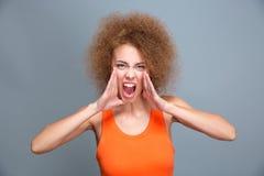 Stående av den ilskna rasande unga lockiga skrikiga kvinnan Arkivbilder