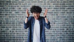 Stående av den ilskna ung flickastudenten som skriker anseende på tegelstenbakgrund lager videofilmer